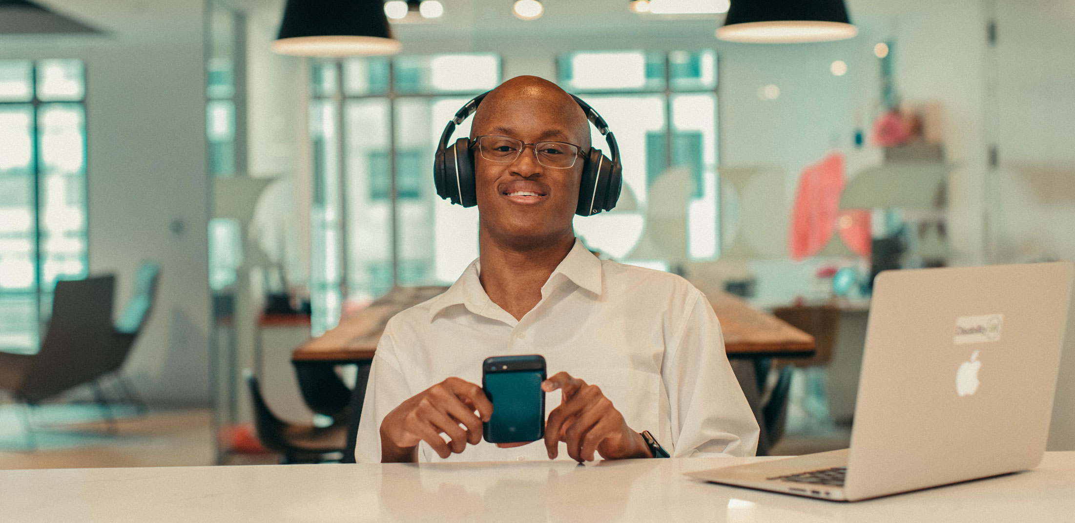 Man wearing headphones and holding a cell phone