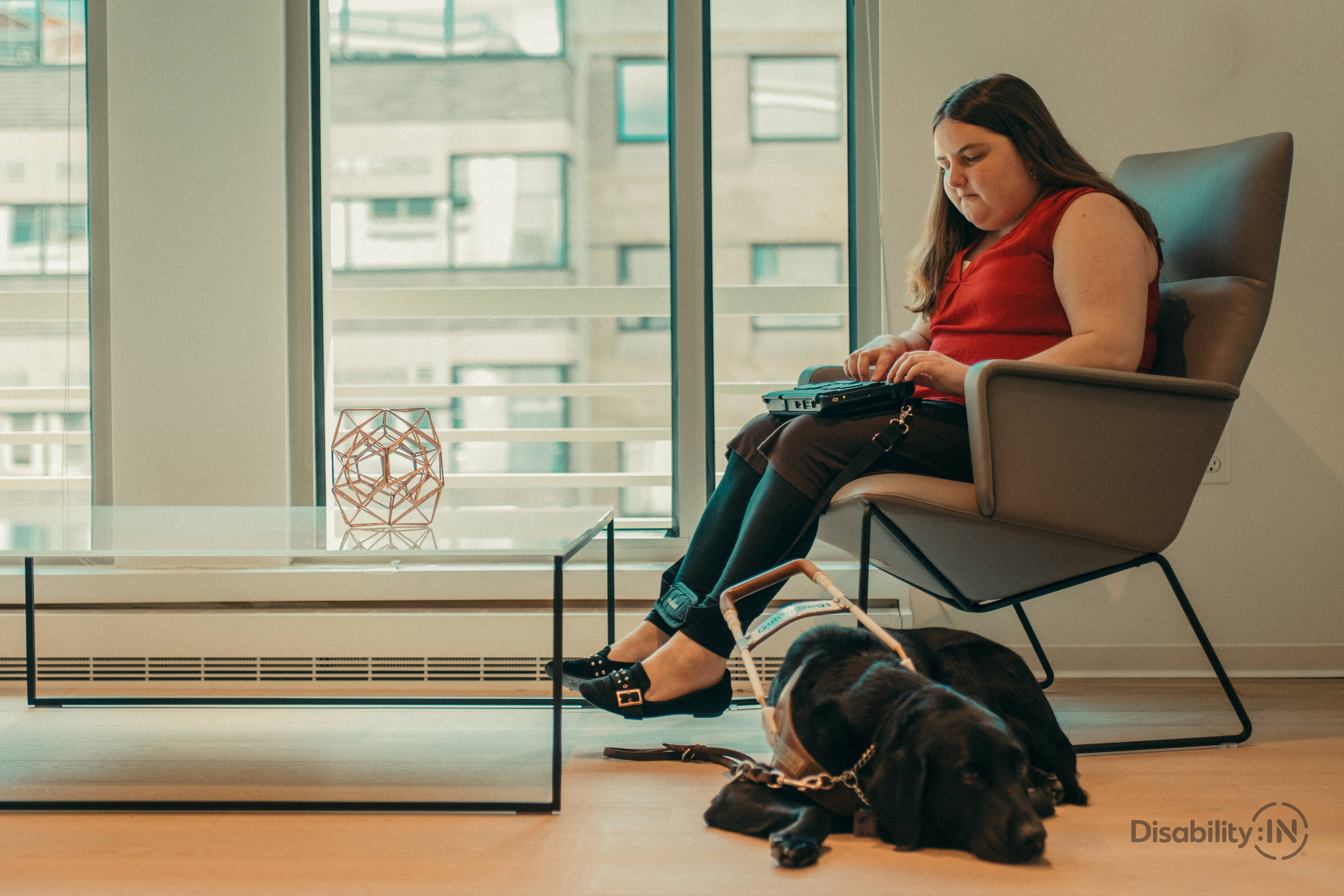 Woman sits on chair taking notes on braille notetaker. Guide dog sits on floor beside her.