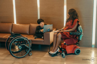 Two women meet informally in a corporate hallway. One woman is a wheelchair user and works on the couch, the other woman is on a motorized chair.