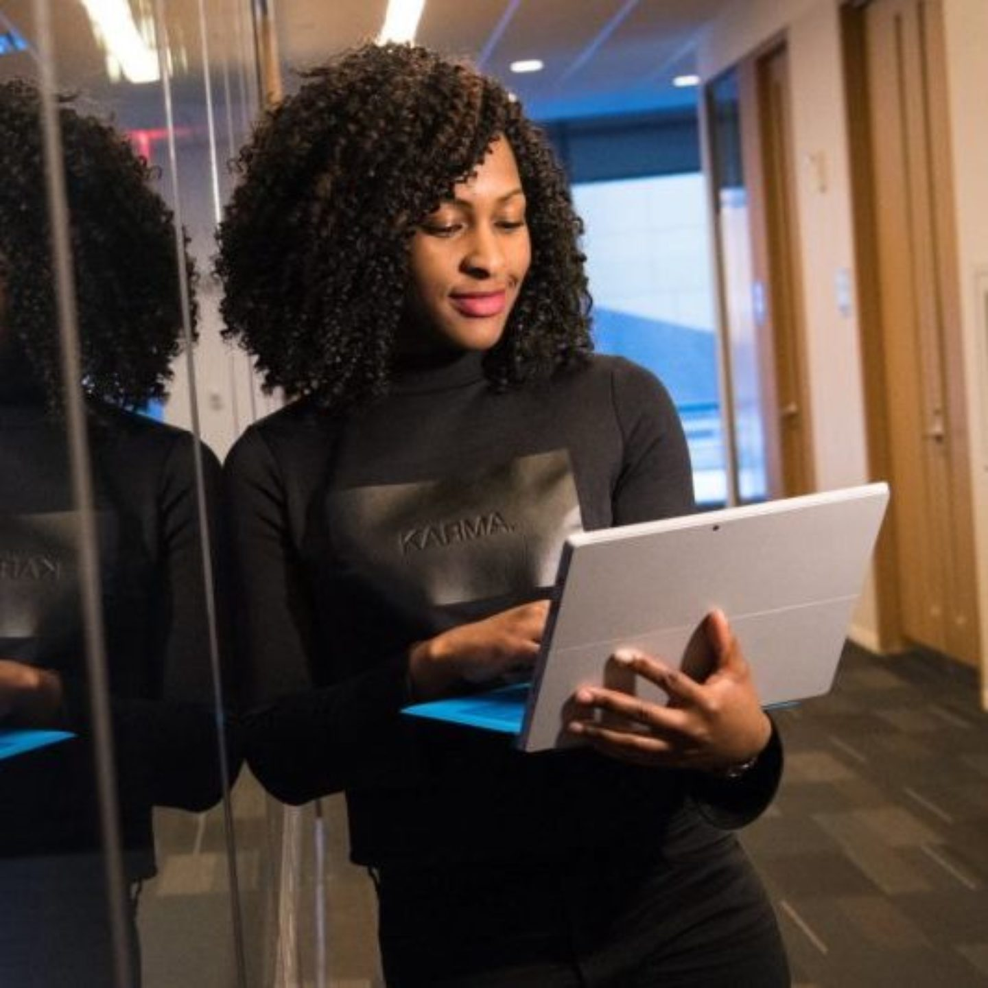 Woman of color with her laptop in front of computer server.
