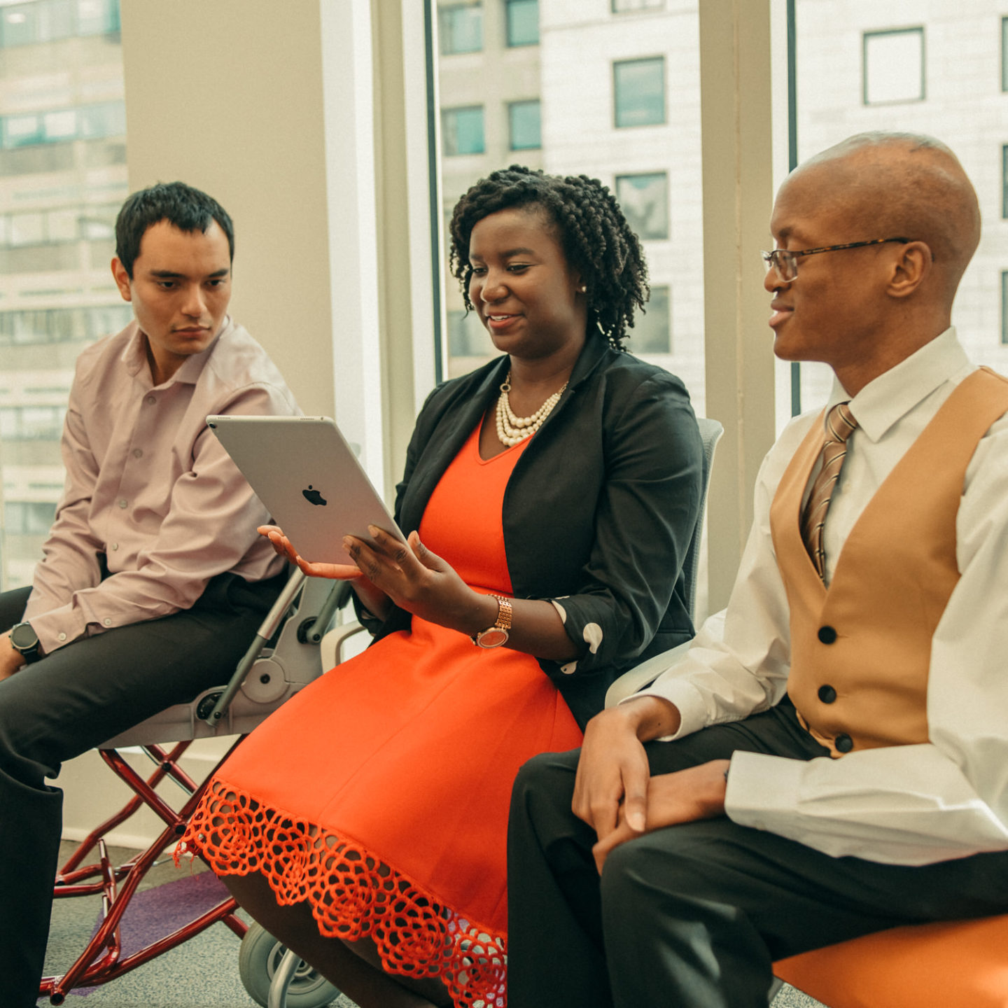 Three diverse individuals sit down next to each other while referencing an iPad tablet in the center of the group.